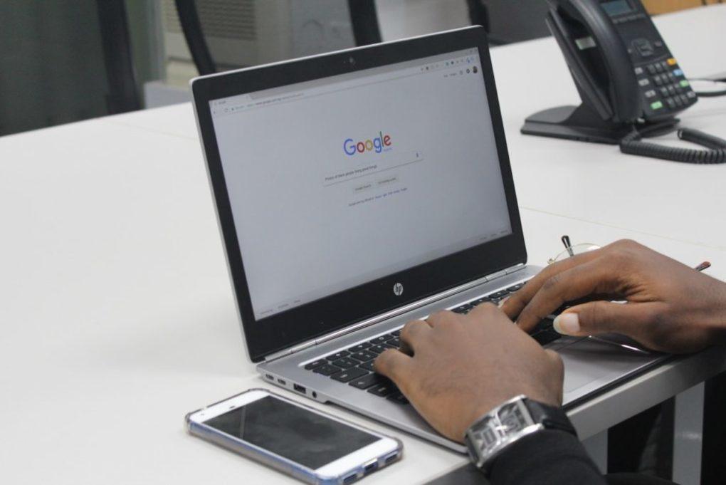 человек ищет в Google, используя ноутбук