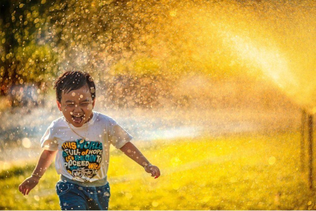 ребенок смеется и бежит по воде, лицо смотрит в камеру